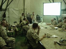 "U.S. Army Civil Affairs officers Lieutenant Colonel Leonardo Rivera and Lieutenant Colonel ""Diesel Joe"" Smith brief incoming Poles on the situation in south-central Iraq. The briefing took place at Camp Babylon on September 2, 2003."