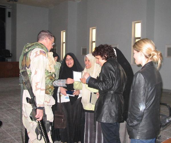 February 2004. The Women's Rights Center in Karbala. Fern Holland, far right and Salwa Oumashi, second from right, pointing to the picture, were killed in Iraq in March 2004.